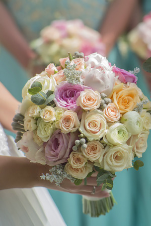 wedding: Closeup of beautiful fresh wedding bouquet of colorful rose flowers pink violet lilac purple white orange and yellow in hands of bride and bridesmaid in blue dresses, horizontal picutre
