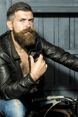 motor cycle: Attractive brutal unshaven sexy male biker in brown leather jacket jeans with sunglasses sitting in garage on motor cycle looking forward on wooden background, vertical picture Stock Photo
