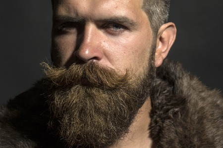 sullen: Porrtait of sullen unshaven guy with long beard and hendlebar moustache in brown fur coat with collar standing on black background, horizontal picture Stock Photo