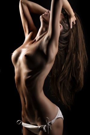 wet breast: One undressed sexy flexible young girl in panties with beautiful teats nipples flat belly and straight wet body standing with raised hands touching long hair on black background, vertical picture Stock Photo