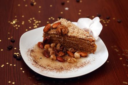 cafe bombon: Pedazo de pastel de nuez fresca deliciosa miel con nueces avellana avellana y almendra en la placa blanca con la orquídea en la mesa de madera con granos de café y oro decorativo estrella bon-bon, imagen horizontal