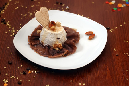 filbert: Vanilla ice cream with filbert walnut hazel and almond nuts drizzled with caramel on chocolate pancake with cookie in shape of heart on white plate wood table with coffee beans and gold stars