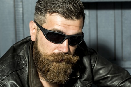 unshaved: Portrait of handsome brutal unshaved male biker with long beard and moustache in brown leather jacket and black sunglasses sitting on grey wooden background, horizontal picture