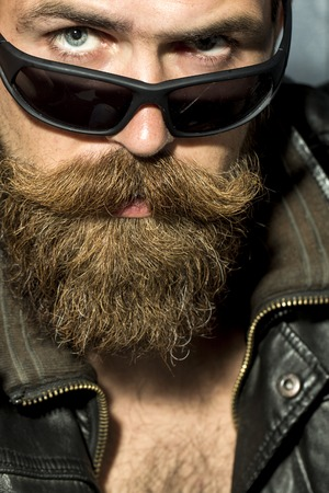 unshaved: Portrait of sexual brutal unshaved guy with long beard and moustache in brown leather biker jacket and black sunglasses looking forward closeup, vertical picture