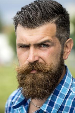Portret van de knappe jonge ongeschoren man met een lange baard en snor hendlebar in de geblokte wit en lichtblauw overhemd verheugen zich openlucht, verticaal beeld Stockfoto