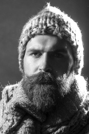 white beard: Portrait of serious unshaven male tramp with long beard and hendlebar moustache in knitted hat and scarf looking forward black and white closeup, vertical picture