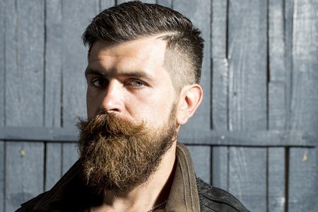 Portret van mooie brutale ongeschoren man met een lange baard en hendlebar in bruin lederen jas kijken ernaar uit zich op grijze houten achtergrond, horizontaal beeld