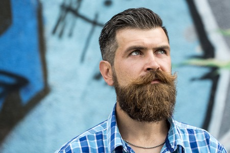 Gloomy serious unshaven guy with long beard and hendlebar moustache in checkered white and light blue shirt looking away standing outdoor on graffiti background copyspace, horizontal picture