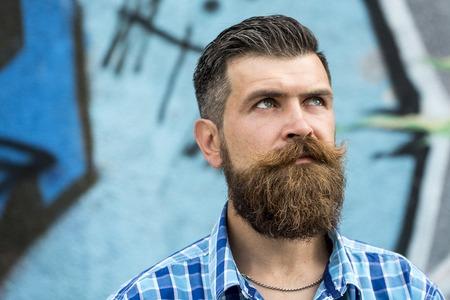 grafitis: Hombre sin afeitar serio melanc�lico con larga barba y bigote hendlebar en camisa blanco y azul claro a cuadros mirando a otro lado de pie al aire libre en fondo de la pintada copyspace, horizontal de la imagen