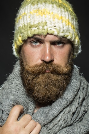 arching: Portrait of unsocial unshaven tramp man with long beard and hendlebar moustache in knitted yellow hat and grey scarf looking forward arching brow standing on black background, vertical picture