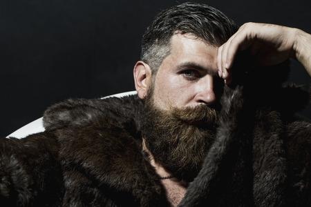 Brutal knappe sullen ongeschoren man met een lange baard en snor in bruin bont jas met kraag zitten in witte badton op een zwarte achtergrond copyspace, horizontaal beeld