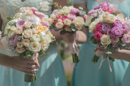 bouquet: Three beautiful fresh wedding bouquets of colorful rose flowers pink violet lilac purple white orange and yellow in hands of bride and bridesmaid in blue dresses, horizontal picutre