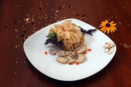 cafe bombon: Panqueque relleno con setas de campo en salsa con albahaca y el perejil en un plato blanco sobre la mesa de madera con los granos de café de flores de color amarillo y la estrella de oro bon-bon, imagen horizontal