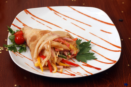 cafe bombon: Crepe relleno de tocino en rodajas dulce rojo verde queso amarillo y salsa con tomate y perejil en un plato blanco sobre la mesa de madera con los granos de caf� y el oro protagoniza bon-bon, foto horizontal