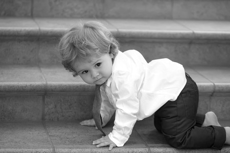 formal shirt: Little curious stylish baby boy with curly hair in formal shirt necktie and trausers creeping barefoot on stone stairs looking away black and white, horizontal picture