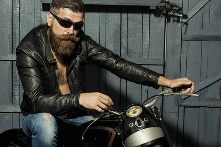 갈색 가죽 재킷 청바지와 회색 나무 배경에 기대 오토바이에 차고에 앉아 태양 안경에 긴 수염을 가진 잘 생긴 잔인한 형태가 이루어지지 않은 남성 바