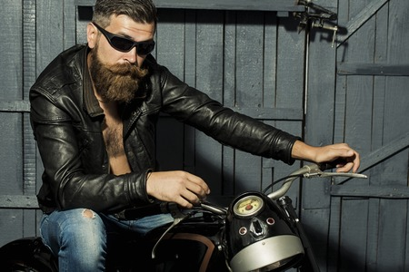Handsome brutal unshaven male biker with long beard in brown leather jacket jeans and sun glasses sitting in garage on motorcycle looking forward on grey wooden background, horizontal picture