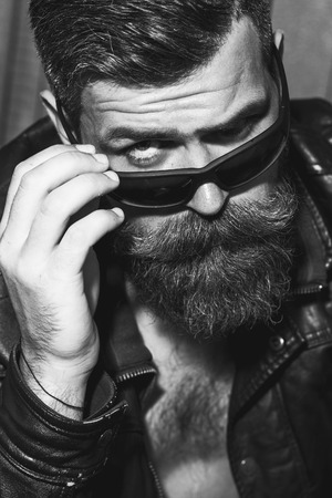 male fashion: Portrait of attractive brutal unshaved male biker with long beard and moustache in leather jacket and sunglasses looking forward black and white, vertical picture