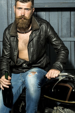 motor cycle: Handsome sexy brutal male biker with long beard and moustache in brown leather jacket with open chest and blue jeans holding glass wine bottle looking forward sitting on motor cycle, vertical picture