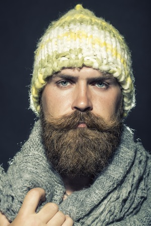 hobo: Portrait of unsocial unshaven hobo man with long beard and hendlebar moustache in knitted yellow hat and grey scarf looking forward standing on black background, vertical picture