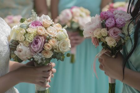 pastel flowers: Decorative beautiful fresh wedding bouquets of colorful rose flowers pink violet lilac purple white orange and yellow in hands of bride and bridesmaid in blue dresses, horizontal picutre Stock Photo