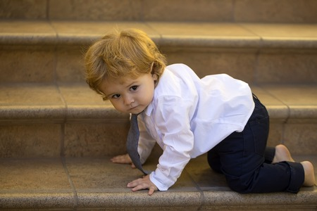 blonde boy: Small curious stylish baby boy with blonde curly hair in formal white shirt grey necktie and trausers crawling barefoot on brown stone stairs looking away, horizontal picture