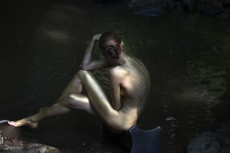 sexy nackte frau: Sch�ne nackte Frau mit sexy Meerjungfrau Gold lackiert K�rper sitzen mit wieder auf steinigem Flussk�ste im Wald in der N�he von Wasser sonnigen Tag im Freien auf die nat�rlichen Hintergrund, horizontale Abbildung