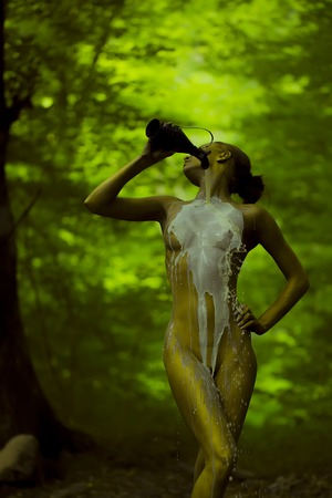 Young girl nymph with gold bodyart pouring white milk from jug on sexual naked female body standing in green deep forest with bare breast nipples belly pubis on natural background, vertical picture