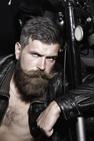 Portrait of serious sexy unshaven man with beard and handlebar moustache in black leather biker jacket with bare torso sitting near motorcycle looking forward, vertical picture