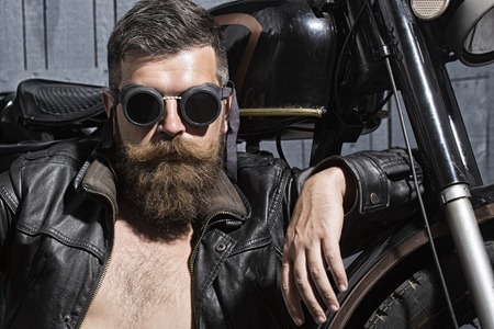 Portrait of serious confident handsome unshaven man with beard and handlebar moustache in leather biker jacket with torso and aviator sunglasses sitting near motorcycle, horizontal picture