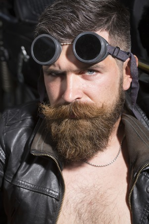 sullen: Portrait of sullen confident attractive sexual unshaven man with beard and handlebar moustache in leather biker jacket with bare torso and aviator sunglasses sitting near motorcycle, vertical picture Stock Photo
