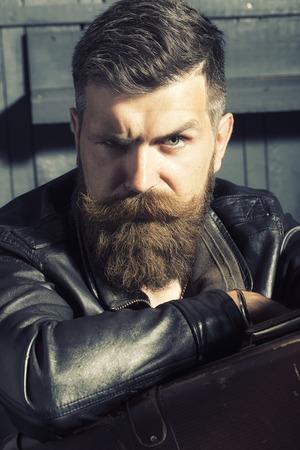 sullen: Portrait of sullen unshaven male biker in black leather jacket sitting in garage with big brown old briefcase looking forward on workshop background, vertical picture