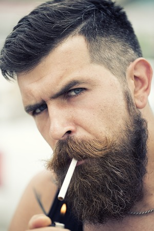 black head and moustache: Portrait of sexual young unshaven man with beard and handlebar moustache smoking cigarette looking forward with expressive face outdoor closeup, vertical picture Stock Photo