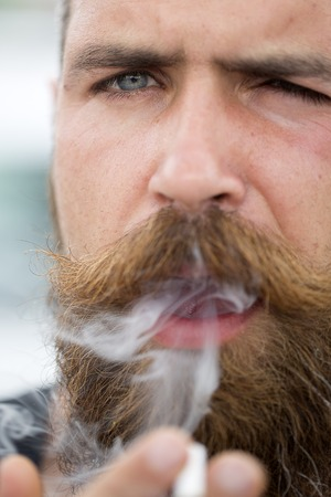 young unshaven: Closeup of sexual young unshaven male face with beard and handlebar moustache of man smoking cigarette looking forward with expressive face outdoor closeup, vertical picture Stock Photo
