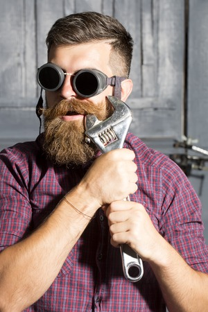 alligator wrench: Poprtrait of young strange man in purple checkered shirt and aviator glasses standing in garage holding iron metallized spanner near mouth on workshop background, vertical picture Stock Photo