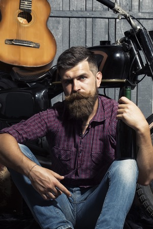 young unshaven: Sexy young musical unshaven man with beard and handlebar moustache in purple checkered shirt and jeans sitting near motorcycle and string acoustic guitar on workshop background, vertical picture