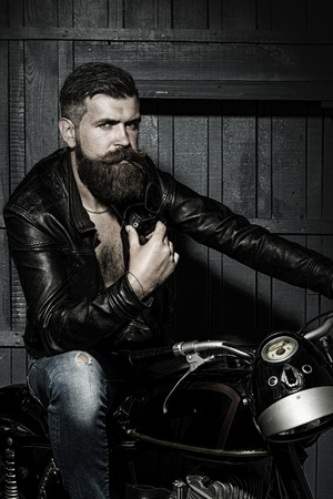 Handsome brutal unshaven sexual male biker in black leather jacket jeans with sun glasses sitting in garage on motor bike looking forward on wooden background, vertical picture