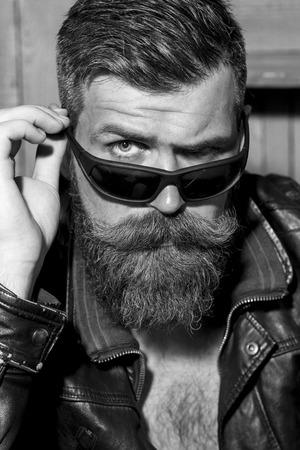 bigote: Retrato de hombre sin afeitar brutal guapo con larga barba y bigote en la chaqueta de motorista de cuero y gafas de sol mirando hacia adelante primer blanco y negro, imagen vertical
