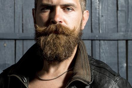Portret van seksuele brutale ongeschoren man met een lange baard en hendlebar in bruin lederen jas kijken ernaar uit zich op grijze houten achtergrond, horizontaal beeld