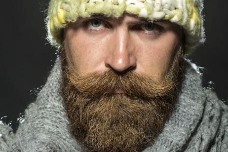 bigote: Retrato de hombre sin hogar sin afeitar triste con larga barba y bigote hendlebar en sombrero amarillo de punto y bufanda gris ganas de pie sobre fondo negro, cuadro horizontal