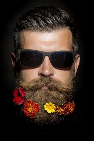 bigote: La pista del hombre sin afeitar sombrío en gafas de sol con larga barba y bigote hendlebar macizo de flores con las maravillas flores de color rojo y amarillo naranja sobre fondo negro, imagen vertical
