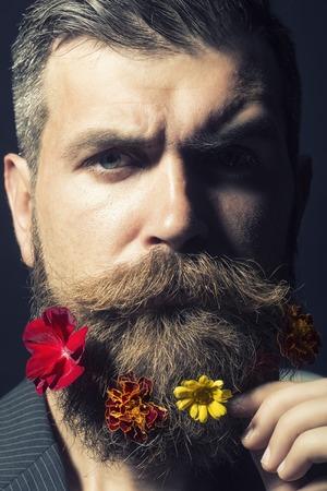 poses de modelos: Retrato del hombre sin afeitar emocional con larga barba y el bigote arriate hendlebar con las maravillas de colores flores de color rojo y amarillo naranja sobre fondo negro primer plano, imagen vertical Foto de archivo