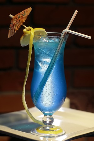 blue lagoon: One glass with alcoholic blue lagoon cocktail of liqueur blue curacao vodka sprite yellow lemon citrus fruit and ice cubes with drink straws and umbrella on brick background, vertical photo Stock Photo