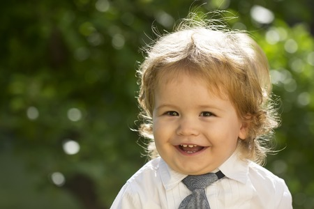 Portrait of smiling boy child with blonde curly hair and round cheeks in white shirt with necktie looking forward sunny day outdoor on natural green tree leaves background copyspace, horizontal photo