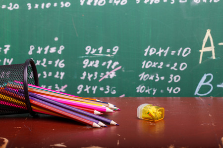 math set: Colorful pencils of red yellow orange violet purple pink green and blue in stationary cup and steel lying on brown school desk on written with white chalk blackboard backgroung on lesson of math