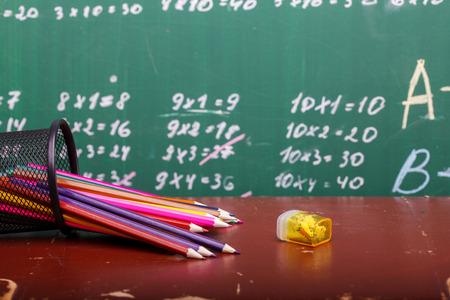 simbolos matematicos: Lápices de colores de rojo anaranjado violeta rosa púrpura verde y azul en la taza fija y acero tendido en escritorio de la escuela marrón en escrito con tiza blanca pizarra backgroung en la lección de matemáticas Foto de archivo