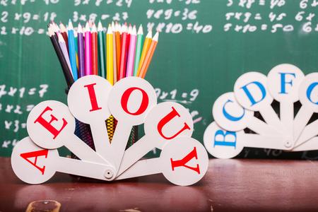 matematica: L�pices de colores de rojo naranja violeta rosa p�rpura verde y azul en la regla taza fija y ventilador alfabeto Ingl�s de pie en la escuela escritorio marr�n en escritos con tiza en la pizarra blanca matem�ticas