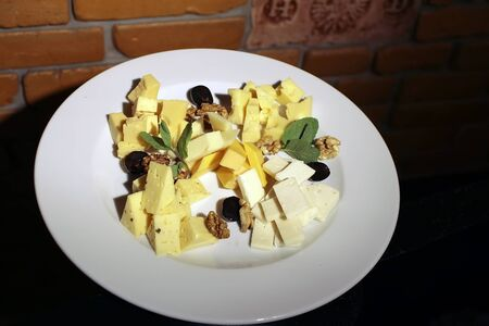 White round plate with many different kinds of cheese yellow color with black olive berry walnut and green leaves on brown brick wall background, horizontal picture