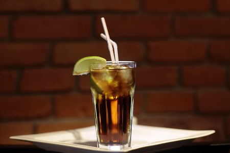 One glass bocal with cold black tea with ice cubes and fresh slice of green yellow citrus lime fruit with two drink straws standing on white plate on brown brick wall background, horizontal picture