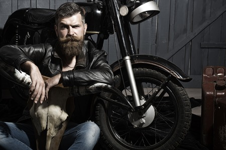 Sullen unshaven male biker in leather jacket sitting near motorcycle in garage with big bone skull antlers of stuffed animal looking forward on wooden wall background, horizontal picture